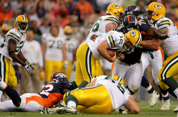 DENVER - AUGUST 22:  Quarterback Aaron Rodgers #12 of the Green Bay Packers is sacked by Elvis Dumervil #92 of the Denver Broncos as Marcus Thomas #79 of the Broncos adds pressure during NFL preseason action at Invesco Field on August 22, 2008 in Denver,