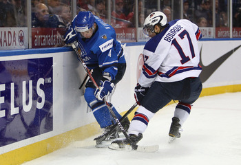 BUFFALO, NY - DECEMBER 26:  Tommi Kivisto #4 of Finland battles for the puck with  Ryan Bourque #17 of USA during the 2011 IIHF World U20 Championship Group A game between USA and Finland on December 26, 2010 at HSBC Arena in Buffalo, New York. (Photo by 
