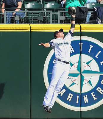 SEATTLE - SEPTEMBER 19:  Center fielder Michael Saunders #55 of the Seattle Mariners makes a leaping catch at the wall on a ball hit by Nelson Cruz #17 of the Texas Rangers at Safeco Field on September 19, 2010 in Seattle, Washington. The Mariners defeate