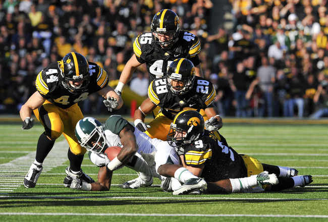 IOWA CITY, IA - OCTOBER 30: Wide receiver Mark Bell #2 of the Michigan State Spartans is tackled by defensive back Tyler Sash #9 of the University of Iowa Hawkeyes as his teammates James Morris #44, Tyler Nielsen #45, and Shaun Prater #28 defend during th