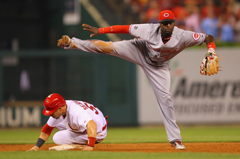 ST. LOUIS, MO - JULY 6: Brandon Phillips #4 of the Cincinnati Reds turns a double play over Skip Schumaker #55 of the St. Louis Cardinals at Busch Stadium on July 6, 2011 in St. Louis, Missouri.  (Photo by Dilip Vishwanat/Getty Images)