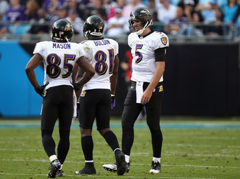 CHARLOTTE, NC - NOVEMBER 21:  Joe Flacco #5 of the Baltimore Ravens talks to his wide receivers Derrick Mason #85 and Anquan Boldin #81 during a timeout against the Carolina Panthers at Bank of America Stadium on November 21, 2010 in Charlotte, North Caro