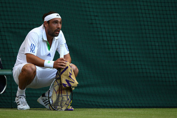 LONDON, ENGLAND - JUNE 25:  Marcos Baghdatis of Cyprus takes a break during his third round match against Novak Djokovic of Serbia on Day Six of the Wimbledon Lawn Tennis Championships at the All England Lawn Tennis and Croquet Club on June 25, 2011 in Lo