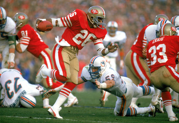 STANFORD, CA - JANUARY 20:  Wendell Tyler #26 of the San Francisco 49ers works to escape a tackle during Super Bowl XIX against the Miami Dolphins at Stanford Stadium on January 20, 1985 in Stanford, California.  The 49ers defeated the Dolphins 38 to16. (