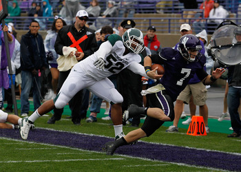 EVANSTON, IL - OCTOBER 23: Dan Persa #7 of the Northwestern Wildcats is knocked out of bounds short of the goalline by Denzel Drone #52 of the Michigan State Spartans at Ryan Field on October 23, 2010 in Evanston, Illinois. Michigan State defeated Northwe