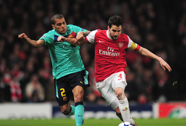 LONDON, ENGLAND - FEBRUARY 16:  Daniel Alves of Barcelona challenges Cesc Fabregas of Arsenal during the UEFA Champions League round of 16 first leg match between Arsenal and Barcelona at the Emirates Stadium on February 16, 2011 in London, England.  (Pho