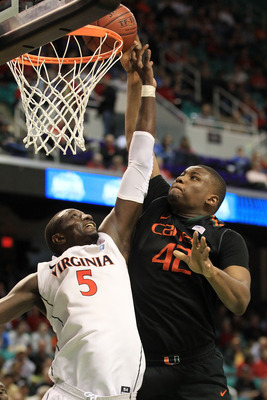 GREENSBORO, NC - MARCH 10:  Reggie Johnson #42 of the Miami Hurricanes shoots against Assane Sene #5 of the Virginia Cavaliers during the second half of the game in the first round of the 2011 ACC men's basketball tournament at the Greensboro Coliseum on