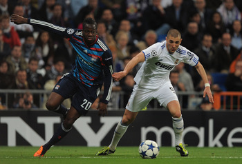 MADRID, SPAIN - MARCH 16: Karim Benzema (R) of Real Madrid gets past Aly Cissokho of Lyon during the UEFA Champions League round of 16 second leg match between Real Madrid and Lyon at Estadio Santiago Bernabeu on March 16, 2011 in Madrid, Spain.  (Photo b