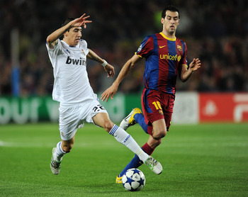 BARCELONA, SPAIN - MAY 03:  Angel Di Maria (L) of Real Madrid duels for the ball with Sergio Busquets of Barcelona during the UEFA Champions League Semi Final second leg match between Barcelona and Real Madrid at the Camp Nou stadium on May 3, 2011 in Bar