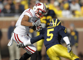 ANN ARBOR, MI - NOVEMBER 20:  Nick Toon #1 of the Wisconsin Badgers tries to get around the tackle of Courtney Avery #5 of the Michigan Wolverines at Michigan Stadium on November 20, 2010 in Ann Arbor, Michigan.  (Photo by Gregory Shamus/Getty Images)
