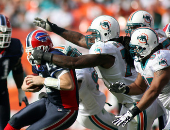 MIAMI - DECEMBER 19:  Defensive tackle Tony McDaniel #94 of the Miami Dolphins sacks quarterback Ryan Fitzpatrick #14 of the Buffalo Bills at Sun Life Stadium on December 19, 2010 in Miami, Florida. The Bills defeated the Dolphins 17-14.  (Photo by Marc S