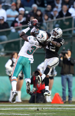 OAKLAND, CA - NOVEMBER 28:  Jacoby Ford #12 of the Oakland Raiders catches the ball while defended by Chris Clemons #30 of the Miami Dolphins at Oakland-Alameda County Coliseum on November 28, 2010 in Oakland, California.  (Photo by Ezra Shaw/Getty Images