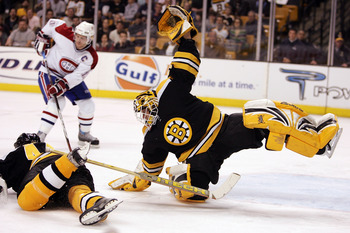 BOSTON - MARCH 22:  Tim Thomas #33 of the Boston Bruins flops to stop the puck as teammate Aaron Ward #44 blocks the shot on March 22, 2007 at the TD Banknorth Garden in Boston, Massachusetts. Saku Koivu #11 of the Motreal Canadiens looks on. (Photo by El
