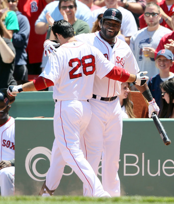 BOSTON, MA - JUNE 04: David Ortiz #34 of the Boston Red Sox congratulates teammate Adrian Gonzalez #28 after Gonzalez hit a solo home run in the first inning against the Oakland Athletics on June 4, 2011 at Fenway Park in Boston, Massachusetts.  (Photo by