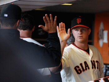 SAN FRANCISCO, CA - JULY 10:  Matt Cain #18 of the San Francisco Giants is congratulated by teammates in the dugout after the sixth inning of their game against the San Francisco Giants at AT&T Park on July 10, 2011 in San Francisco, California.  (Photo b