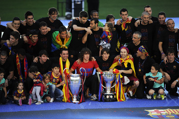 BARCELONA, SPAIN - MAY 29:   FC Barcelona players pose with the La Liga Tropy and the UEFA Champions League trophy during the celebrations after winning the UEFA Champions League Final against Manchester United at Camp Nou Stadium on May 29, 2011 in Barce