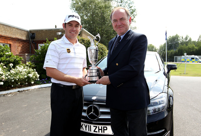 SANDWICH, ENGLAND - JULY 11:  2010 Open Champion Louis Oosthuizen (L) of South Africa returns the Claret Jug to Peter Dawson, chief executive of The R&A during the first practice round during The Open Championship, at Royal St. George's on July 11, 2011 i