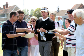SANDWICH, ENGLAND - JULY 11:  Bubba Watson of USA signs autographs for the fans during the first practice round during The Open Championship, at Royal St. George's on July 11, 2011 in Sandwich, England. The 140th Open begins on July 14, 2011.  (Photo by A