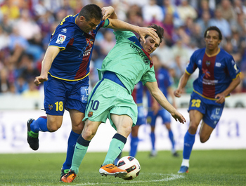 VALENCIA, SPAIN - MAY 11:  Lionel Messi (R) of Barcelona competes for the ball with Sergio Ballesteros of Levante during the La Liga match between Levante UD and Barcelona at Ciutat de Valencia on May 11, 2011 in Valencia, Spain.  (Photo by Manuel Queimad