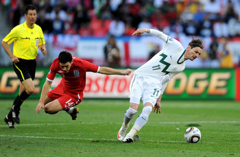 PORT ELIZABETH, SOUTH AFRICA - JUNE 23: Milivoje Novakovic of Slovenia is challenged by Gareth Barry of England during the 2010 FIFA World Cup South Africa Group C match between Slovenia and England at the Nelson Mandela Bay Stadium on June 23, 2010 in Po