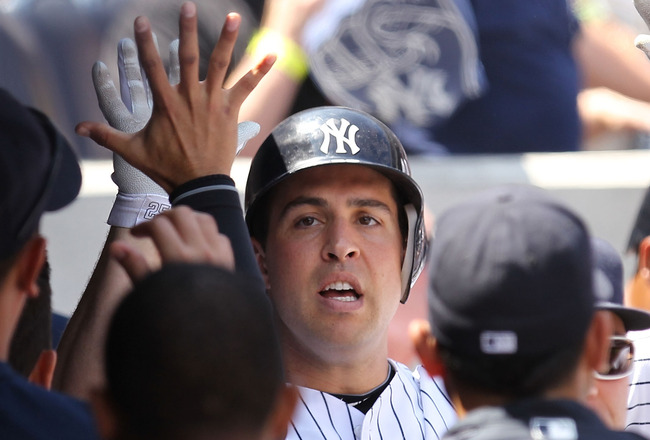 NEW YORK, NY - JUNE 30:  Mark Teixeira #25 of the New York Yankees celebrates with teamates after hitting a solo home run in the third inning against the Milwaukee Brewers during their game on June 30, 2011 at Yankee Stadium in the Bronx borough of New Yo