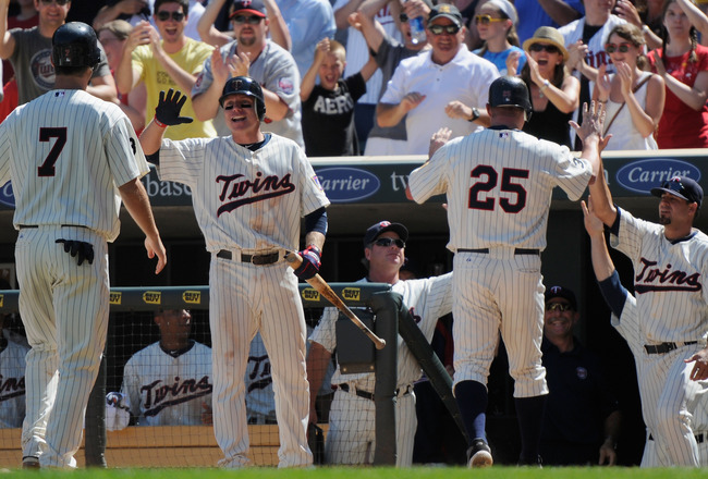MINNEAPOLIS, MN - JULY 3: Joe Mauer #7, Luke Hughes #38, Jim Thome #25 and Jason Repko #18 of the Minnesota Twins celebrate the Twins taking the lead in the seventh inning against the Milwaukee Brewers on July 3, 2011 at Target Field in Minneapolis, Minne