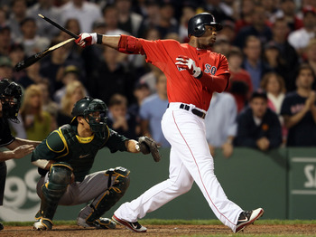 BOSTON, MA - JUNE 03:  Carl Crawford #13 of the Boston Red Sox hits a 2 RBI single in the seventh inning as Kurt Suzuki #8 of the Oakland Athletics defends on June 3, 2011 at Fenway Park in Boston, Massachusetts.  (Photo by Elsa/Getty Images)