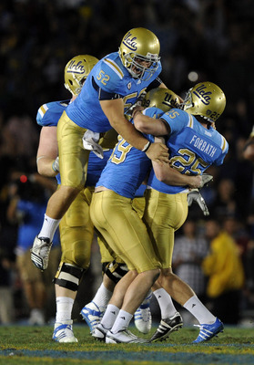 PASADENA, CA - NOVEMBER 06:  Kai Forbath #25 of the UCLA Bruins gets a hug from Danny Rees #39 and Christian Yount #52 in celebration of a last second field goal to win the game 17-14 over the Oregon State Beavers during the fourth quarter at the Rose Bow