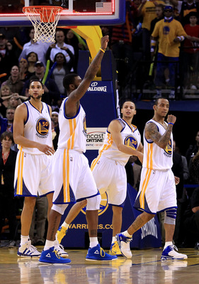 OAKLAND, CA - JANUARY 21:  Dan Gadzuric #50, Dorell Wright #1, Stephen Curry #30 and Monta Ellis #8 of the Golden State Warriors reacts after the Warriors sent their game against the Sacramento Kings into overtime at Oracle Arena on January 21, 2011 in Oa