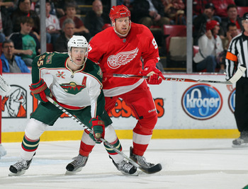 DETROIT,MI - NOVEMBER 19:  Nick Schultz #55 of the Minnesota Wild defends against Johan Franzen #93 of the Detroit Red Wings in a game on November 19, 2010 at the Joe Louis Arena in Detroit, Michigan. The Wild defeated the Wings 4-3 in overtime. (Photo by