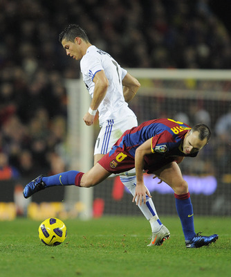 BARCELONA, SPAIN - NOVEMBER 29:   Cristiano Ronaldo (L) of Real Madrid  duels for the ball with Andres Iniesta of FC Barcelona during the La Liga match between Barcelona and Real Madrid at the Camp Nou Stadium on November 29, 2010 in Barcelona, Spain.  Ba