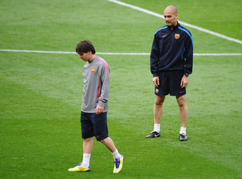 LONDON, ENGLAND - MAY 27:  Lionel Messi of FC Barcelona (L) walks as Josep Guardiola manager of FC Barcelona looks on during a Barcelona training session prior to the UEFA Champions League final versus Manchester United at Wembley Stadium on May 27, 2011