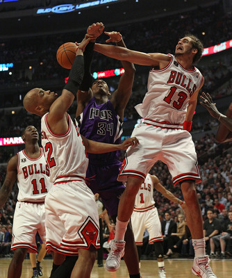 CHICAGO, IL - MARCH 21: Joakim Noah #13 of the Chicago Bulls blocks a shot by Jason Thompson #34 of the Sacramento Kings as teammate Taj Gibson #22 also defends at the United Center on March 21, 2011 in Chicago, Illinois. NOTE TO USER: User expressly ackn