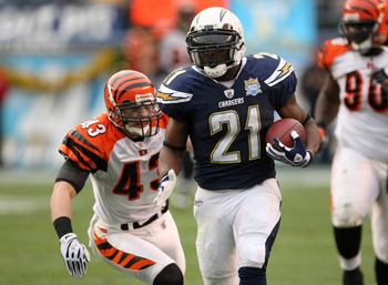 SAN DIEGO - DECEMBER 20:  Running back LaDainian Tomlinson #21 of the San Diego Chargers carries the ball past safety Tom Nelson #43 of the Cincinnati Bengals on December 20, 2009 at Qualcomm Stadium in San Diego, California.  The Chargers won 27-24.  (Ph
