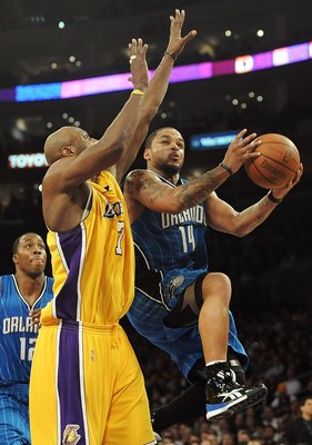 LOS ANGELES, CA - JANUARY 18:  Jameer Nelson #14 of the Orlando Magic goes to the basket against Lamar Odom #7 of the Los Angeles Lakers during the game on January 18, 2010 at Staples Center in Los Angeles, California. The Lakers won 98-92. NOTE TO USER: