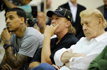 EL SEGUNDO, CA - MAY 31:  Jim Buss, (C) executive vice president of basketball operations of the Los Angeles Lakers, team owner Jerry Bus and player Matt Barnes listen to new coach Mike Brown's speach during his introductory news conference at the team's
