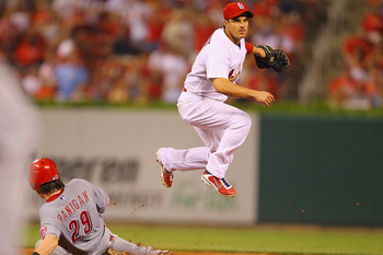 ST. LOUIS, MO - JULY 6: Ryan Theriot #3 of the St. Louis Cardinals turns a double play over Ryan Hanigan #29 of the Cincinnati Reds at Busch Stadium on July 6, 2011 in St. Louis, Missouri.  (Photo by Dilip Vishwanat/Getty Images)