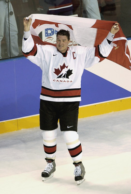 SALT LAKE CITY - FEBRUARY 24:  Team Captain Mario Lemieux of Canada celebrates by skating on the ice with the Canadian flag over his head after Canada defeated the USA 5-2 to win the gold medal in Men's Hockey at the 2002 Salt Lake City Winter Olympic Gam