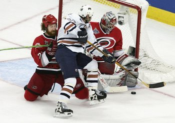 RALEIGH, NC - JUNE 19:  Ryan Smyth #94 of the Edmonton Oilers attempts a shot on goaltender Cam Ward #30 of the Carolina Hurricanes during game seven of the 2006 NHL Stanley Cup Finals on June 19, 2006 at the RBC Center in Raleigh, North Carolina.  (Photo