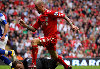 LIVERPOOL, ENGLAND - APRIL 23:  Colin Doyle of Birmingham City dives to make a save at the feet of Raul Meireles of Liverpool during the Barclays Premier League match between Liverpool and Birmingham City at Anfield on April 23, 2011 in Liverpool, England