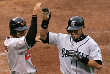 SAN FRANCISCO - JULY 10:  American League All-Star Ichiro Suzuki #51 of the Seattle Mariners celebrates with teammate Brian Roberts #1 of the Baltimore Orioles after Suzuki's inside the park home run in the fifth inning of the 78th Major League Baseball A