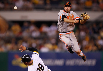 PITTSBURGH - JUNE 21:  J.J. Hardy #2 of the Baltimore Orioles turns the double play over Xavier Paul #38 of the Pittsburgh Pirates during the game on June 21, 2011 at PNC Park in Pittsburgh, Pennsylvania.  (Photo by Jared Wickerham/Getty Images)