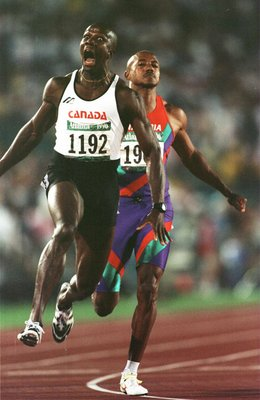 27 Jul 1996: Donovan Bailey of Canada celebrates after winning the men''s 100 meters sprint at Olympic Stadium in Atlanta, Georgia. Bailey finished in 9.84 seconds, a new world record. Behind him, finishing second, is race favorite Frankie Fredericks of N