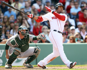 BOSTON, MA - JUNE 04:  Carl Crawford #13 of the Boston Red Sox hits a 2 RBI double in the eighth inning as Landon Powell #11 of the Oakland Athletics catches on June 4, 2011 at Fenway Park in Boston, Massachusetts.  (Photo by Elsa/Getty Images)
