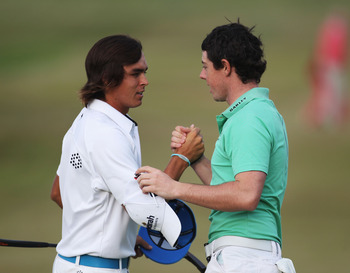 SANDWICH, ENGLAND - JULY 15:  Rickie Fowler of the United States and Rory McIlroy of Northern Ireland shake hands on the 18th green during the second round of The 140th Open Championship at Royal St George's on July 15, 2011 in Sandwich, England. (Photo b