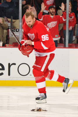 DETROIT - MAY 4:  Tomas Holmstrom #96 of the Detroit Red Wings looks at an octopus thrown on the ice before Game Three of the Western Conference Semifinals against the San Jose Sharks during the 2011 NHL Stanley Cup Playoffs on May 4, 2011 at Joe Louis Ar