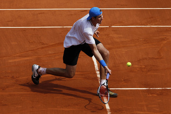PARIS, FRANCE - MAY 24:  John Isner of USA hits a forehand during the men's singles round one match between Rafael Nadal of Spain and John Isner of USA on day three of the French Open at Roland Garros on May 24, 2011 in Paris, France.  (Photo by Matthew S