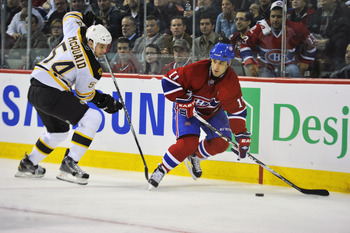 MONTREAL, QC - APRIL 18:  Scott Gomez #11 of the Montreal Canadiens controls the puck in behind the net while being pursued by Adam McQuaid #54 of the Boston Bruins in Game Three of the Eastern Conference Quarterfinals during the 2011 NHL Stanley Cup Play