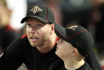 PHOENIX, AZ - JULY 11:  National League All-Star Roy Halladay #34 of the Philadelphia Phillies looks on with his son Ryan during the 2011 State Farm Home Run Derby at Chase Field on July 11, 2011 in Phoenix, Arizona.  (Photo by Christian Petersen/Getty Im
