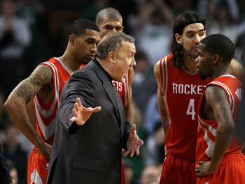 BOSTON, MA - JANUARY 10:  Head coach Rick Adelman of the Houston Rockets talks with Aaron Brooks #0 as Shane Battier #31,Kyle Lowry #7 and Luis Scola #4 stand by during a time out in the final seconds of the game against the Boston Celtics on January 10,